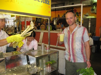 Steve enjoying a sugar cane refreshing juice at Rusty's Markets, in Cairns.