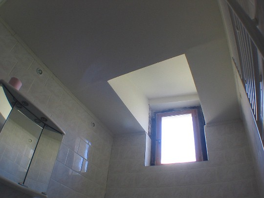 The cieling of the bathroom was about fifteen feet high. It was impossible to warm, and the exposed rock walls made it forever dusty. I built this neat suspended ceiling, still allowing for natural light and for the window to open.